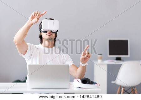 New technical improvements. Pleasant man sitting at the table and being involved in work while using virtual reality device