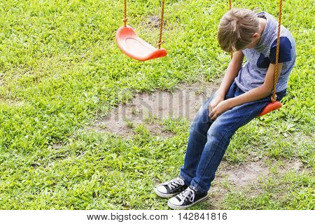 Sad boy sitting on swings at outdoor playground. Sad lonely depressed unhappy mood