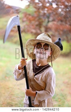 A young child is dressed in a scary Scarecrow hallowen costume on a fall day.
