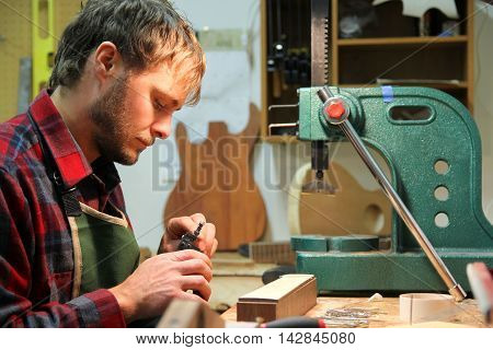 A young man in a flannel shirt is working as a luthier using tools to building a guitar in his home workshop.