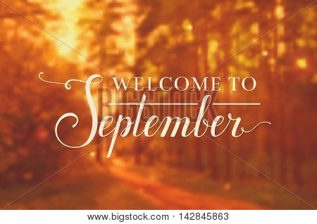 Welcome to September. Blurred autumn background with lettering. Vector banner.