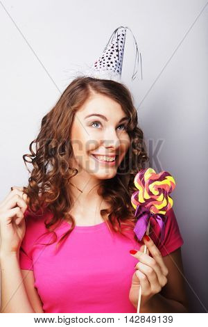 Funny curly woman  holding big lollipop. Birthday party.