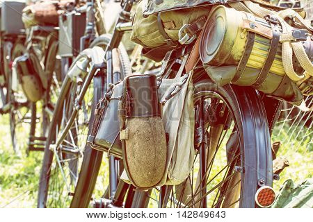 Close up photo of old military bicycle with kitbag and equipments. Backpack and containers for food and drink. Vintage scene. Yellow photo filter. Equipment of german soldier in World War II.