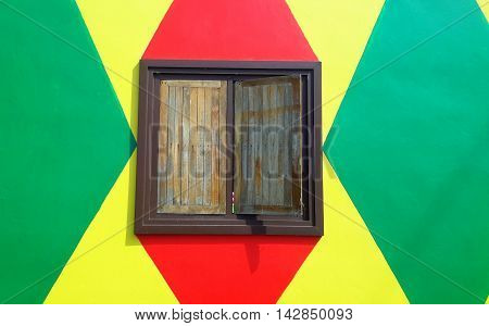 varnished wooden shutters with right shutter slightly ajar, appearing on wall painted alternate red and green diamond shapes on a yellow background, Songkhla, Thailand