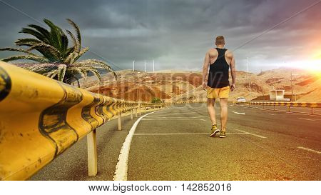 young man as a tourist in a parking lot with guard rails next to a palm tree in Madeira