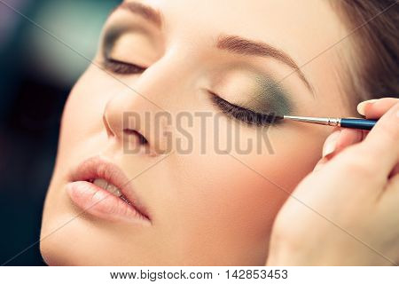 Make-up artist applying liquid eyeliner on model's eyes close up