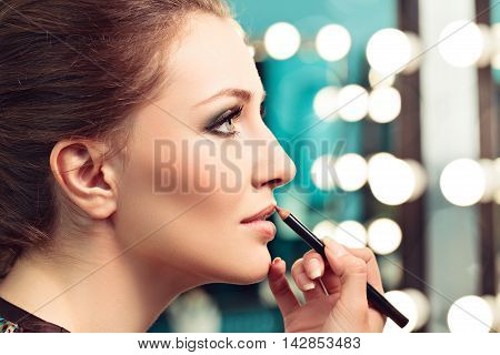 Make-up artist applying lip liner on model's lips focus on model's eye