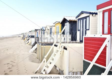 beach huts or houses and clear blue sky. Multicolored beach huts in in a row.