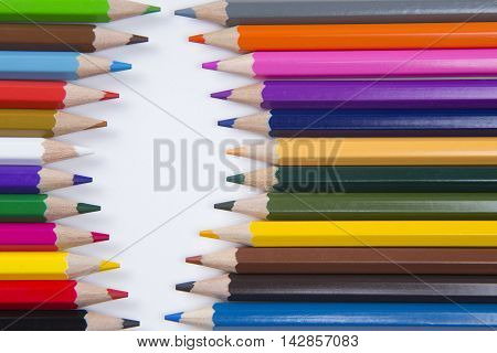 Pencils arranged to face eachother on white paper