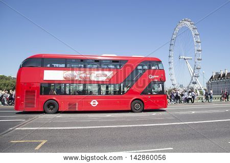 Red London Bus Drives Over Westminster Bridge With London Eye In Background