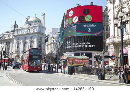 Red Bus Passing Busy Street And Large Screen In Piccadilly Circus