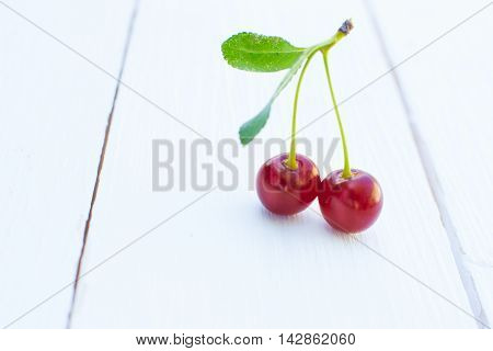 Two Cherries With A Tail On The Wooden Table