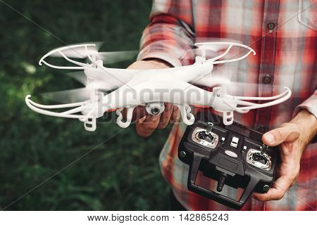 Operator holding remote control and quadrocopter. Unmanned aerial copter starting in forest. Aeromodelling, hobby, leisure concept
