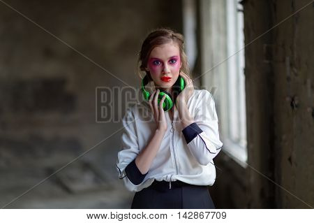 Young beautiful girl with headphones in abandoned urban background