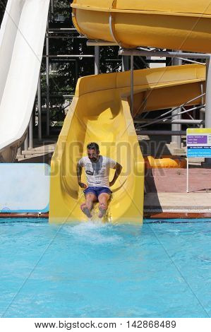 18TH JULY 2016, CALIS,TURKEY:An englishman having fun on a water slide in a waterpark while on vacation in calis, turkey, 18th july 2016