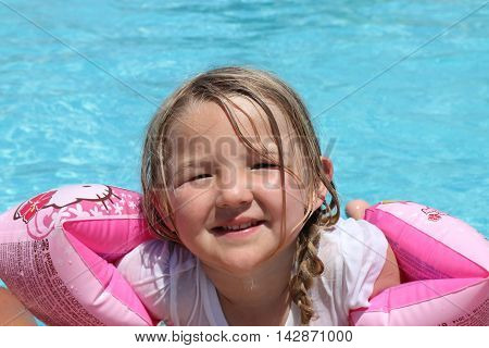 18TH JULY 2016, CALIS, TURKEY; A young girl wearing armbands as floatation aids in a swimming pool while on vacation in calis, turkey, 18th july 2016