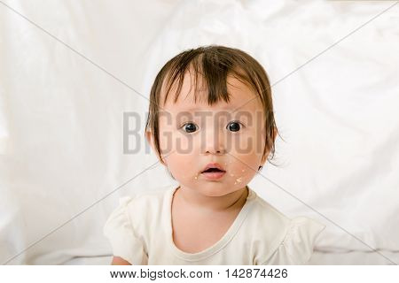 Baby girl eating eye looking to mother, with dirty face
