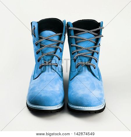 female blue leather boots over white background