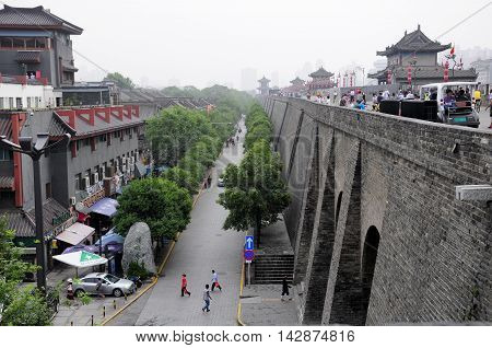 August 19 2015. Xian China. Chinese tourists walking on the Xian city wall as it rises up above the streets in Shaanxi province China on an overcast cloudy day.