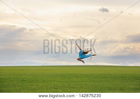 Young woman in blue dress with robbon jumping on grass over gloomy cloudscape