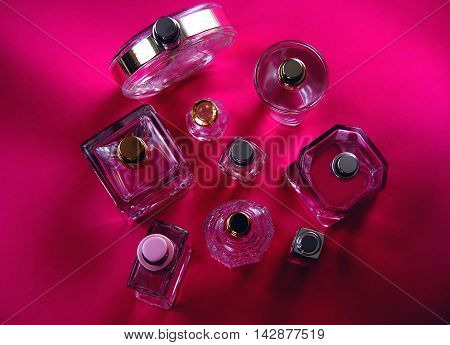 Bottle with perfumes on a pink background
