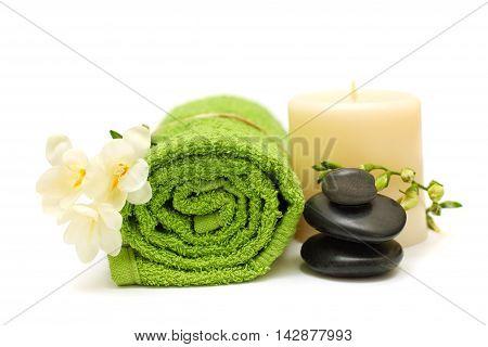 Spa concept - black stones white flower green towel