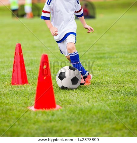 Kid playing soccer. Training football session for children. Boys is training with soccer ball and bollards on the grass pitch