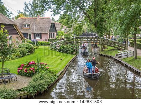 GIETHOORN, NETHERLANDS - AUGUST 9, 2016: Tourists moving a traditional punter boat through the canals of Giethoorn, Holland