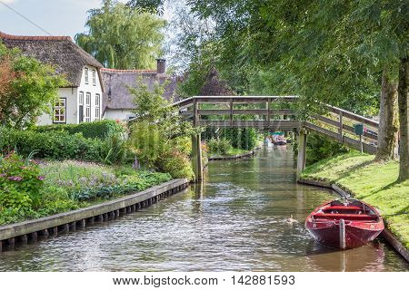 GIETHOORN, NETHERLANDS - AUGUST 9, 2016: Traditional red punter boat in the canals of Giethoorn, Netherlands