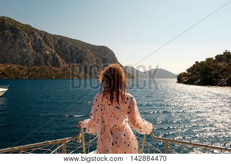 Woman stading ahead on a bow of the boat with beautiful sea scenery
