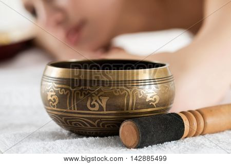 Nepal Buddha copper singing bowl at spa salon with young beautiful woman at background. Sound therapy recreation meditation healthy lifestyle and body care concept