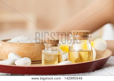 Bottles with aromatic massage oils standing at spa salon. Skin and body care healthy lifestyle relaxation massage and cosmetology concept. Focus on bottles with oils poster