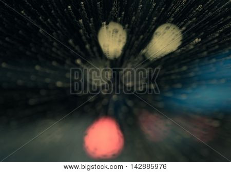 Blurred night raindrops on windscreen bokeh and traffic lights trail background. Motion zoom blur with retro filtered effect.
