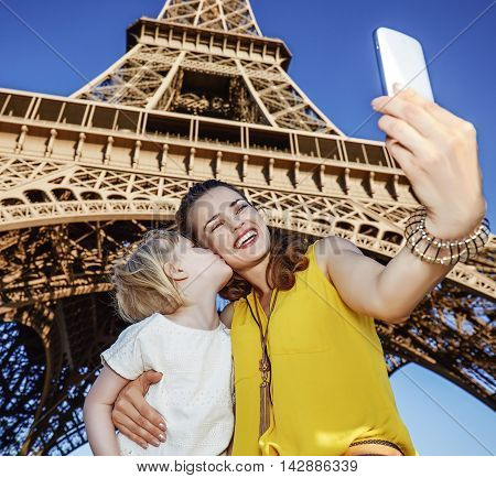 Mother And Daughter Tourists Taking Selfie Near Eiffel Tower