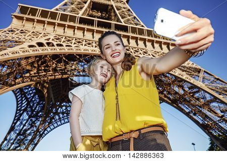 Mother And Child Tourists Taking Selfie Against Eiffel Tower