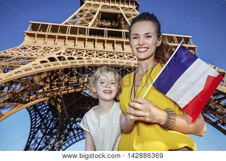 Mother And Daughter Tourists Showing Flag Against Eiffel Tower