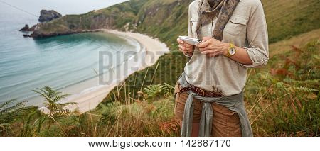 Happy Woman Hiker Writing Sms In Front Of Ocean View Landscape