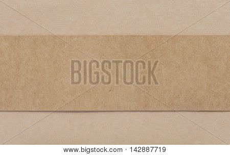 Blank dark brown paper on light brown cardboad background