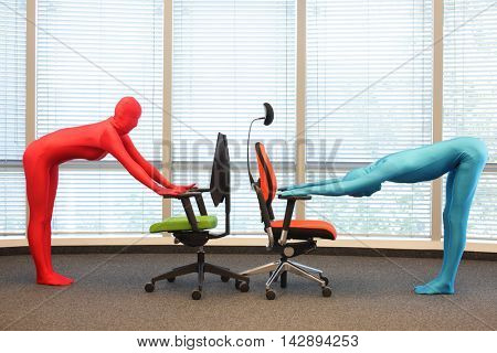 anonymous couple in full body elastic suits exercising with chairs in office