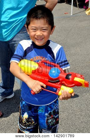 New York City - July 18 2010: Little boy holds his big Super-Soaker water gun at the 16th annual ThinGyan Burmese Water Festival