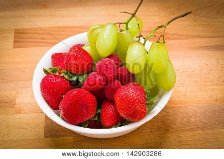Healthy after school snack grapes raspberries strawberries and a white bowl on a wood background