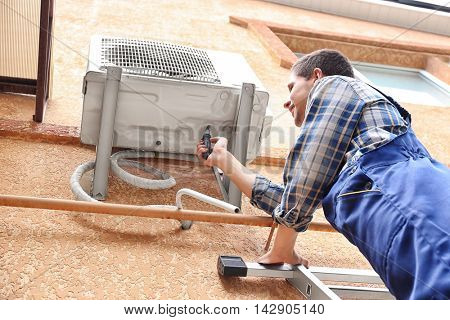 Technician repairing air conditioner on wall outside