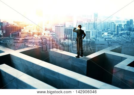 Businessperson on top of concrete maze wall looking into the distance on city background with sunlight