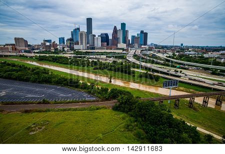 Lower Aerial Bayou River and Railroad Crossing Towers Skyscrapers and Large Downtown Houston Texas Aerial Photography high above Highways and Loops and Interchanges of Urban Sprawl