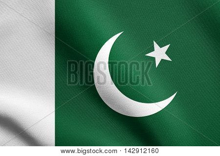 Flag of Pakistan waving in the wind with detailed fabric texture. Pakistani national flag.