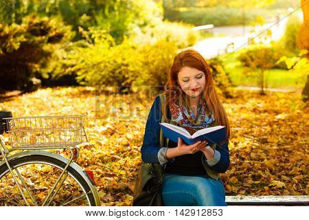 Fall lifestyle concept. Redhaired young woman girl relaxing in autumn park reading book sitting alone on bench. Sunny day