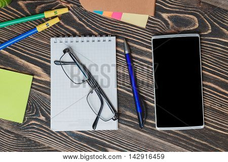 Education Concept. School and Office Supplies with Smartphone on Wooden Background.