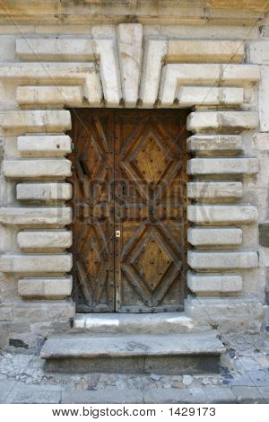 massive wooden door with a stony wall all around poster