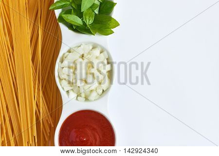 Basil sliced onions and tomato paste in white bowl with raw spaghetti scattered around on white background. Concept image for Italian cuisine. Top view with plenty of copy space