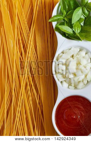 Basil sliced onions and tomato paste in white bowl with raw spaghetti scattered around. Concept image for Italian cuisine. Top view with copy space